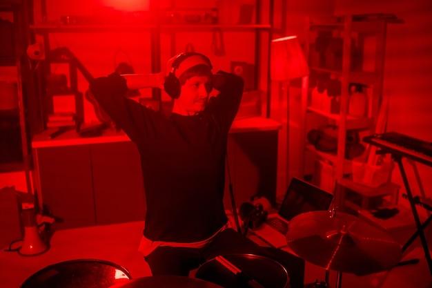 그는 drumset 옆에 앉아있는 동안 그의 스튜디오에서 녹음 한 음악을 듣고 캐주얼웨어와 헤드폰의 젊은 편안한 음악가