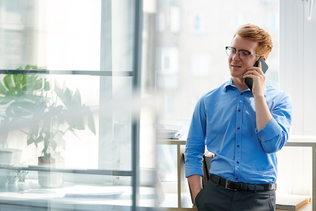 Young restful office worker consulting someone on smartphone while standing by window