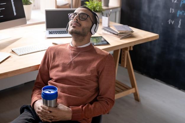 休憩中に彼の職場に対して椅子に座っている間、飲み物とマグカップを保持しているヘッドフォンで若い安らかなプログラマー