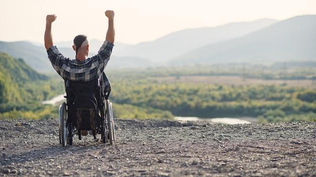 山の晴れた日に新鮮な空気を楽しんでいる車椅子の若い引退した軍人