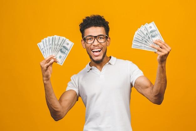Молодой богатый афроамериканец в повседневной футболке с долларовыми купюрами