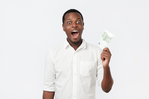Young rich african american man in shirt holding one hundred euro with surprise