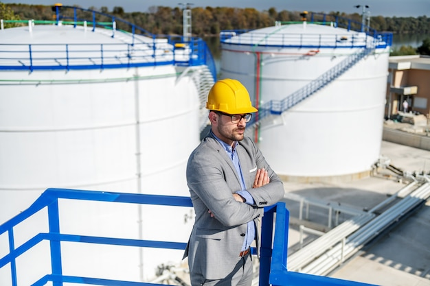 Young rich businessman in suit with helmet on head standing on height with arms crossed and looking around. refinery exterior.