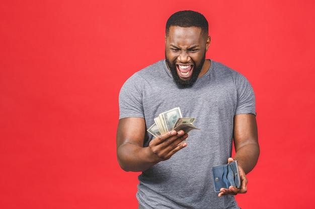 驚きのお金のドル札と財布を持ってカジュアルに若い金持ちの幸せなアフリカ系アメリカ人の男