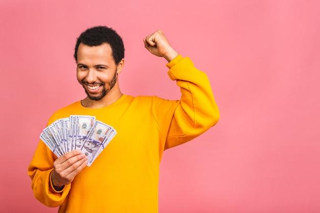 Молодой богатый счастливый человек в непринужденной обстановке держит долларовые банкноты с сюрпризом, изолированными над розовой стеной