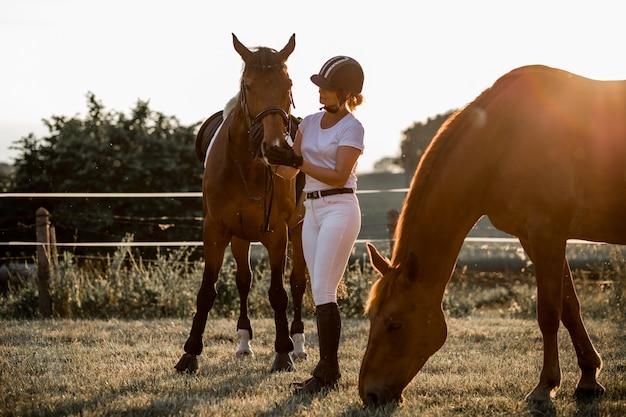 흰색 스포츠 유니폼을 입고 헬멧을 쓴 젊은 라이더는 두 번째 말을 훈련시킨 후 그녀의 말과 대화하고 있는 그녀의 동물에 대한 사랑과 이해의 개념 옆에 서 있습니다