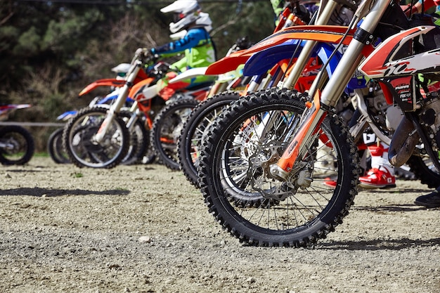 Young riders on motorcycles at starting line during cup winter motocross