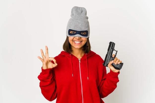 陽気で自信を持って大丈夫なジェスチャーを示すマスクを身に着けている若い強盗ヒスパニック系女性。