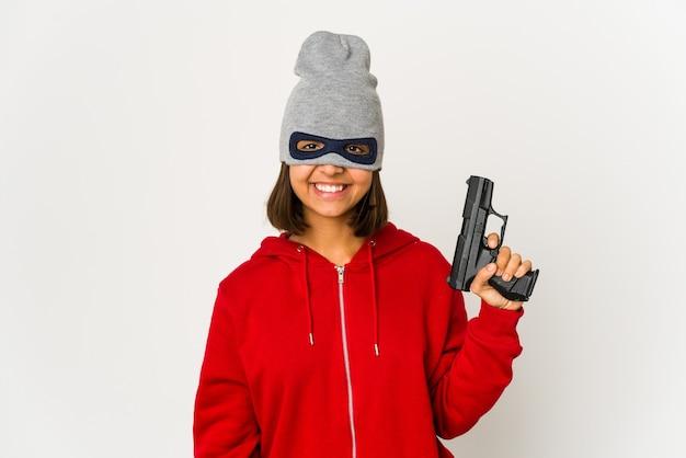Молодой грабитель испаноязычный женщина в маске счастливой, улыбающейся и веселой.