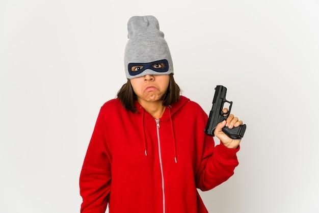 マスクを身に着けている若い強盗ヒスパニック系女性は肩をすくめ、目を開けて混乱しました。