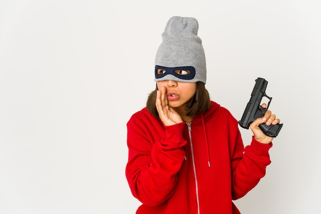 Young robber hispanic woman wearing a mask is saying a secret hot braking news and looking aside