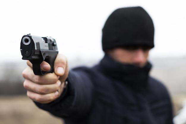 젊은 강도는 권총 근접 촬영 범죄 개념을 쏘고