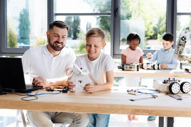 Молодой учитель робототехники сидит за столом со своим учеником