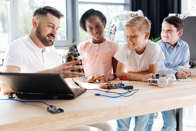 Молодой учитель робототехники сидит за столом со своими учениками