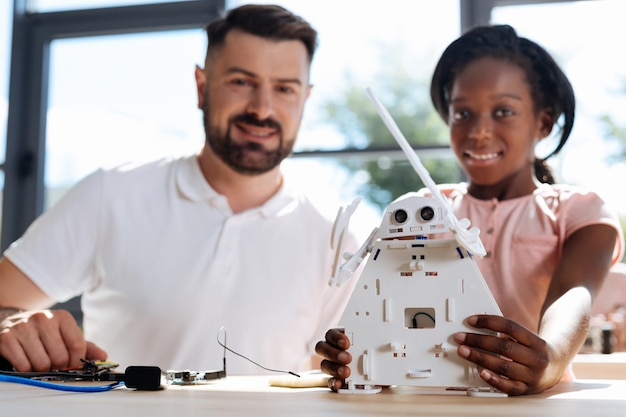 Young robotics teacher sitting at the table with his student