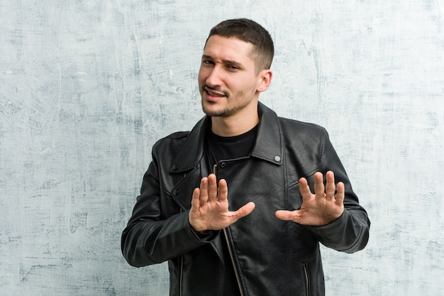 Young rocker man rejecting someone showing a gesture of disgust.