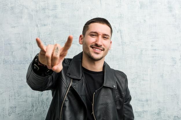Young rocker man showing a horns gesture as a revolution .