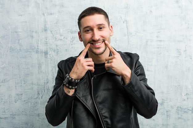 젊은 로커 남자 미소, 입에서 손가락을 가리키는.