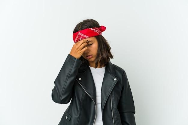 Молодая женщина-рокер, изолированная на белой стене, боится закрывать глаза руками