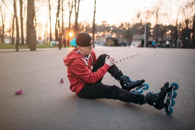 都市公園のアスファルトに座っている若いローラースケート選手。男性ローラースケート選手、エクストリームスポーツ