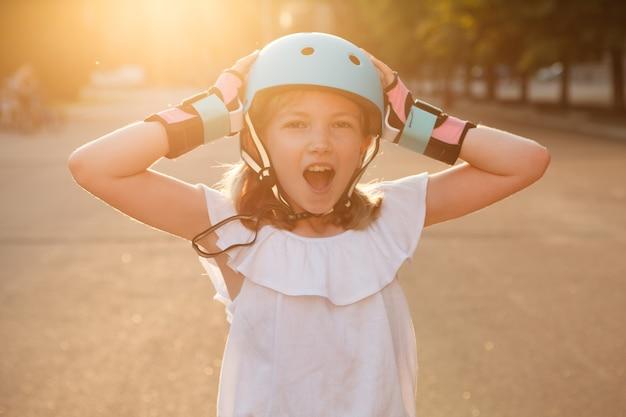 Young rollerblader girl screaming joyfully, wearing helmet outdoors