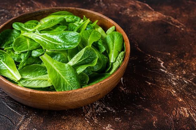 Молодые листья зеленого салата ромен в деревянной тарелке. темный фон. вид сверху. скопируйте пространство.