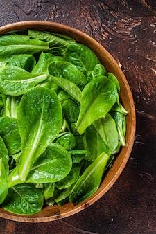 Молодые листья зеленого салата ромен в деревянной тарелке. темный фон. вид сверху.
