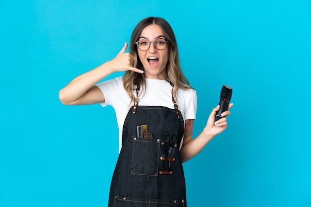 Молодая румынская женщина парикмахера изолированная на голубой стене делая жест телефона. перезвони мне знак