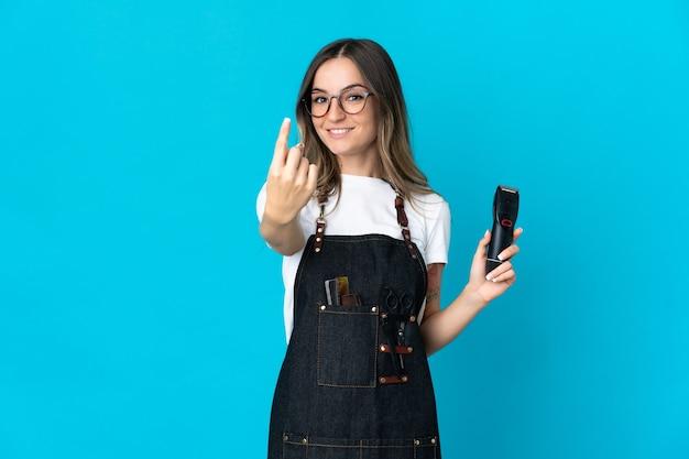Молодая румынская женщина-парикмахер на синем делает приближающийся жест