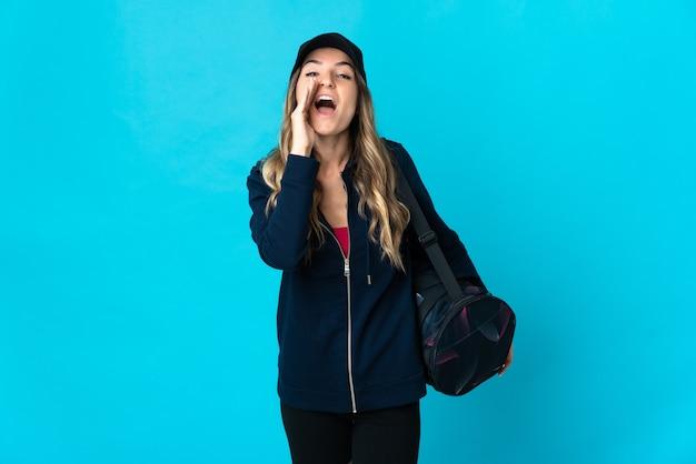 Молодая румынская спортивная женщина со спортивной сумкой изолирована на синей стене и кричит с широко открытым ртом