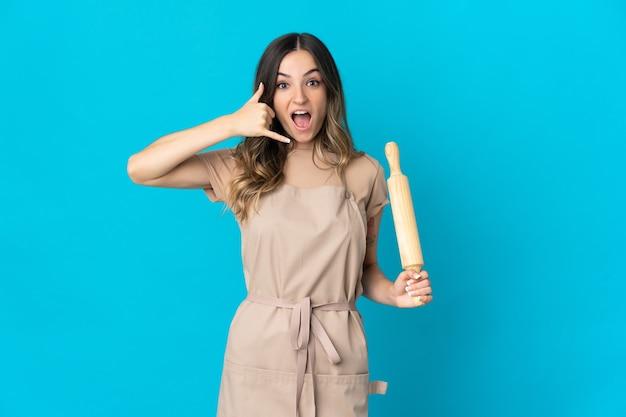 Молодая румынская женщина, держащая скалку, изолированную на синей стене, делая жест телефона. перезвони мне знак