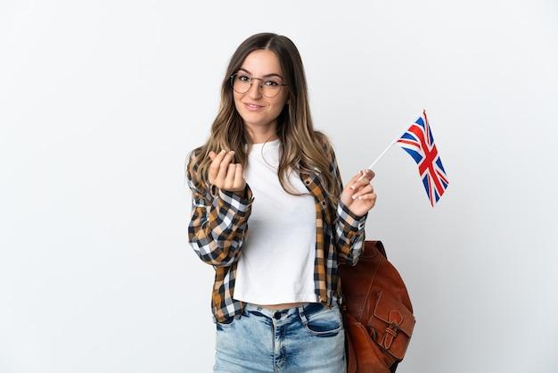 お金のジェスチャーを稼ぐ白い壁に分離されたイギリスの旗を保持している若いルーマニアの女性