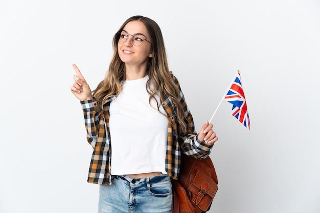 Молодая румынская женщина держит флаг соединенного королевства на белой стене, указывая на отличную идею