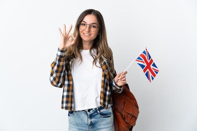 Молодая румынская женщина, держащая флаг соединенного королевства на белом, показывает пальцами знак ок