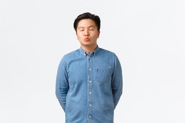 파란색 셔츠를 입은 젊은 낭만적인 아시아 남자, 눈을 감고 키스를 기다리는 것처럼 삐죽삐죽하고, 여자 친구와 데이트를 하고, 감정을 고백하고, 카메라를 향해 기대고, 흰색 배경에 서 있습니다.