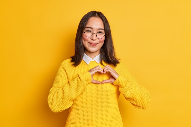 Young romantic asian woman with tender face expression shapes heart gesture expresses love to boyfriend wears round spectacles and knitted sweater.