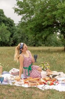 若いロマンチックなブルネットの女性は緑の芝生で屋外のピクニックを楽しみ、白ワインのグラスを保持します。