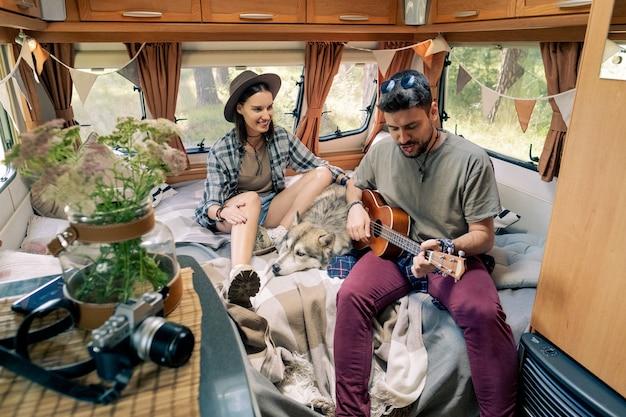 Молодая романтическая пара и их домашнее животное наслаждаются летними каникулами в передвижном доме