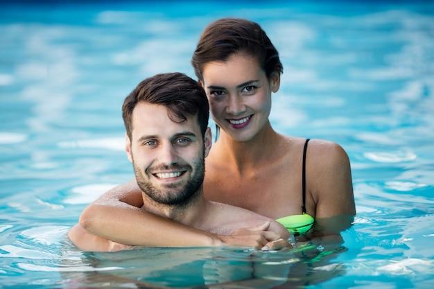 수영장에서 서로 껴 안은 젊은 낭만적 인 부부