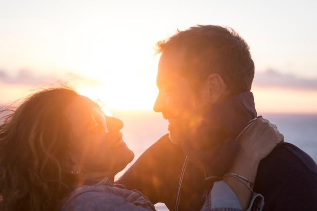일몰 동안 야외에서 껴안은 젊은 로맨틱 커플. 휴가에 여가 시간을 보내는 사랑하는 부부의 닫습니다. 서로 얼굴을 마주보며 웃는 다정한 커플
