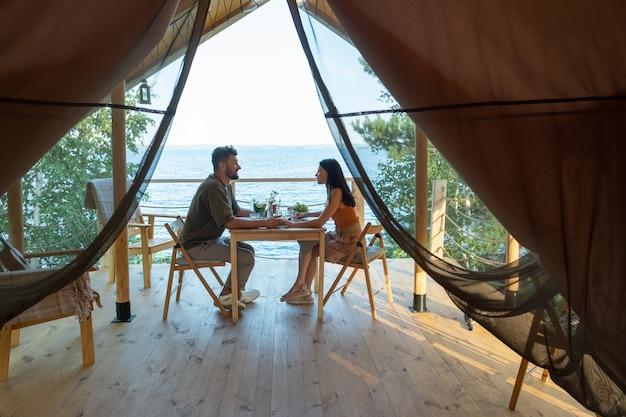 Молодая романтическая пара, наслаждаясь завтраком на террасе на берегу моря