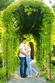Молодая романтическая пара весело провести время, наслаждаясь друг другом в зеленом летнем парке.