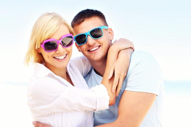 ビーチで抱き締める若いロマンチックなカップル