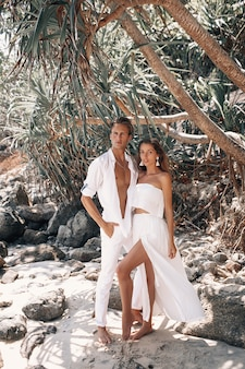 熱い熱帯のビーチで抱き締めてポーズをとって白い服を着た若いロマンチックなカップル