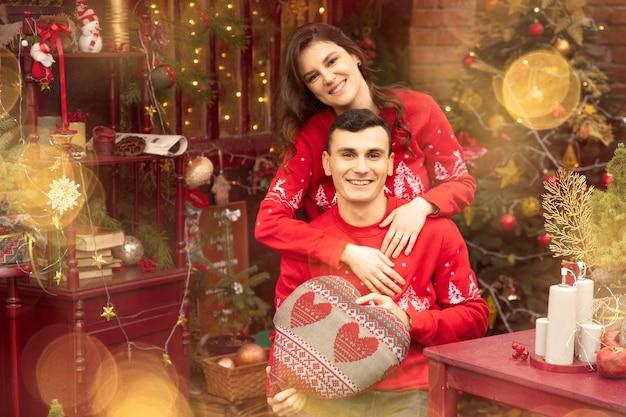 Молодая романтическая пара веселится на открытом воздухе зимой перед рождеством. с удовольствием проводят время вместе в канун нового года. двое влюбленных обнимаются в день святого валентина.