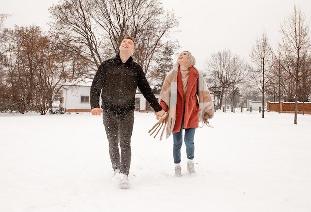 젊은 낭만적 인 부부는 겨울에 야외에서 재미입니다. 두 연인이 세인트 발렌타인 데이 스토리에서 포옹과 키스를하고 있습니다.
