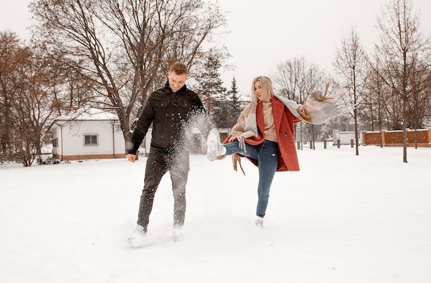 Молодая романтическая пара веселится на открытом воздухе зимой. двое влюбленных обнимаются и целуются в день святого валентина.