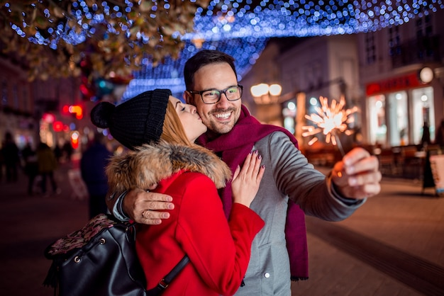 Young romantic couple is having fun with bengal lights in the winter city street.