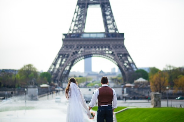 Young romantic couple near the eiffel tower at early morning in paris, france