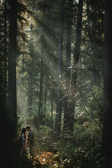 Young romantic couple of pretty woman with long brunette hair and bearded man holding hands walking in green sunny forest